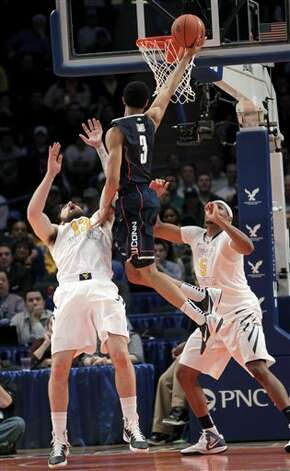 Connecticut's Jeremy Lamb, center, makes the basket and is fouled by West Virginia's Deniz Kilicli, left, while Kevin Jones looks on during the second round of the Big East NCAA college basketball conference tournament in New York, Wednesday, March 7, 2012. (AP Photo/Seth Wenig)