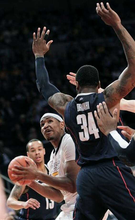 West Virginia's Kevin Jones, left, looks looks to shoot past Connecticut's Alex Oriakhi (34) during the second round of the Big East NCAA college basketball conference tournament in New York, Wednesday, March 7, 2012. (AP Photo/Seth Wenig)