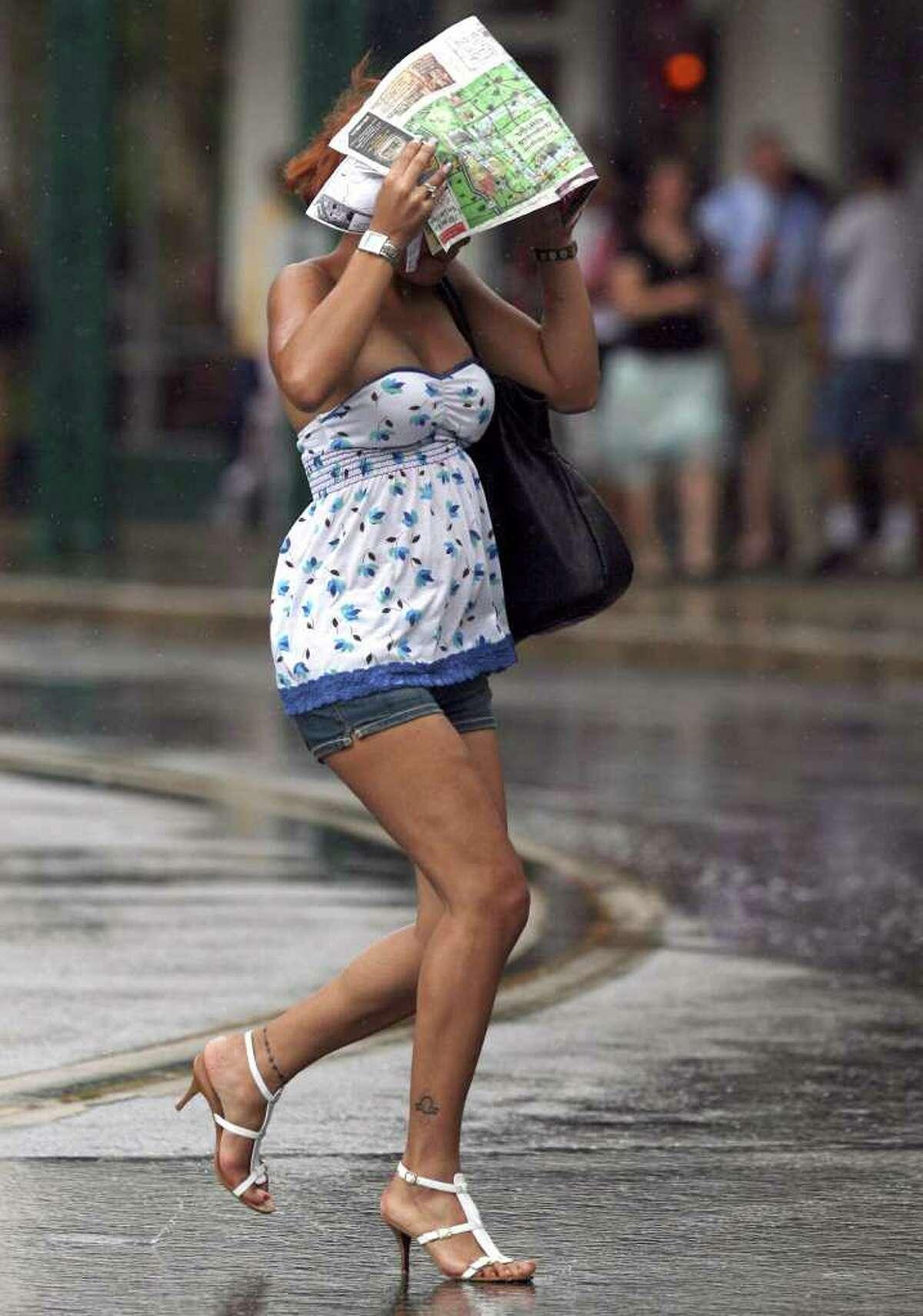Joanna Estevez covers her head as she crosses Alamo Plaza during a rain storm on Monday July 7, 2008. JOHN DAVENPORT/jdavenport@express-news.net