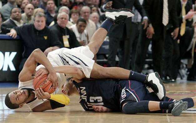 West Virginia's Gary Browne, left, and Connecticut's Shabazz Napier fight for a ball during the second round of the Big East NCAA college basketball conference tournament in New York, Wednesday, March 7, 2012. Connecticut beat West Virginia in overtime 71-67. (AP Photo/Seth Wenig)