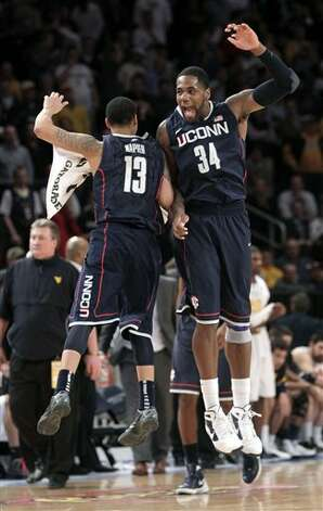 Connecticut's Shabazz Napier, left, and Alex Oriakhi celebrate their win over West Virginia during the second round of the Big East NCAA college basketball conference tournament against West Virginia in New York, Wednesday, March 7, 2012. Connecticut beat West Virginia in overtime 71-67. (AP Photo/Seth Wenig)