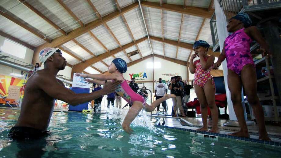 Cullen Jones, an Olympic gold medalist, left catches Helena Carnot, 5, during a swimming class he's instructing for the Make a Splash program, Wednesday, March 7, 2012, at the Clay Road Family YMCA in Houston. Make a Splash is a national child focused safety initiative, with the help of ConocoPhillips, reaching 1.1 million people since it's inception teaching water safety in 47 states. Photo: Nick De La Torre, Houston Chronicle / © 2012  Houston Chronicle