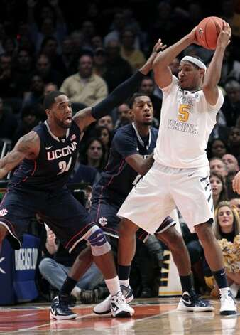 West Virginia's Kevin Jones, right, is defended by Connecticut's Alex Oriakhi during the second round of the Big East NCAA college basketball conference tournament in New York, Wednesday, March 7, 2012. Connecticut beat West Virginia in overtime 71-67. (AP Photo/Seth Wenig)