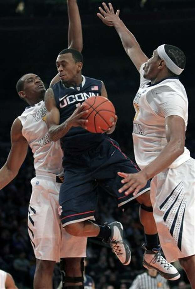 Connecticut's Ryan Boatright, center, jumps past West Virginia's Dominique Rutledge, left, and Kevin Jones during the second round of the Big East NCAA college basketball conference tournament in New York, Wednesday, March 7, 2012. Connecticut beat West Virginia in overtime 71-67. (AP Photo/Seth Wenig)