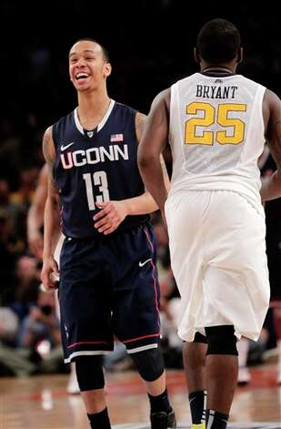 Connecticut's Shabazz Napier reacts after making a basket during the second round of the Big East NCAA college basketball conference tournament against West Virginia in New York, Wednesday, March 7, 2012. At right is West Virginia's Darryl Bryant. Connecticut beat West Virginia in overtime 71-67. (AP Photo/Seth Wenig)