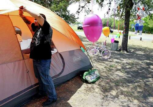 FOR METRO - Joe Urdialez III adjusts his family's tent Friday April 22, 2011 at Woodlawn Lake. The Urdialez were camping with the Mireles family and have been celebrating Easter at the lake for the past two years. Both families said they moved their Easter celebration from Brackenridge Park because of the crowds. (PHOTO BY EDWARD A. ORNELAS/eaornelas@express-news.net) Photo: EDWARD A. ORNELAS, SAN ANTONIO EXPRESS-NEWS / SAN ANTONIO EXPRESS-NEWS (NFS)