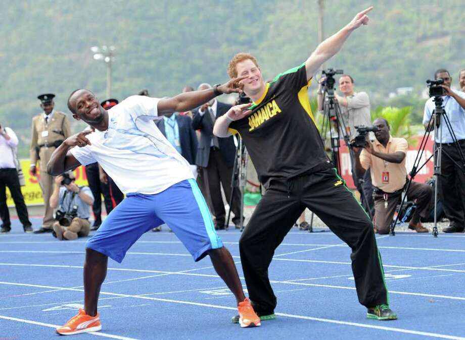 Britain's Prince Harry and Usain Bolt, Jamaica's champion do the lightening strike pose, on the track at the University of the West Indies in Kingston, Jamaica on March 6, 2012. Prince Harry gave Bolt a run for his money Tuesday. Minutes after teaching the prince the basics of starting, Bolt was surprised to see his royal competitor race 50 meters down the track, in what would be described internationally as a false start. AFP PHOTO/Anthony FOSTER Photo: ANTHONY FOSTER, AFP/Getty Images / AFP