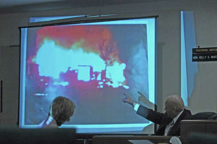 Buskirk Fire Chief Michael Moses, right, points up to a photograph projected onto a screen in Washington County Court on Wednesday, March 7, 2012 in Fort Edward, NY.  The photograph is of the home that Matthew Slocum is accused of setting fire to after shooting his family members inside.    (Paul Buckowski / Times Union) Photo: Paul Buckowski