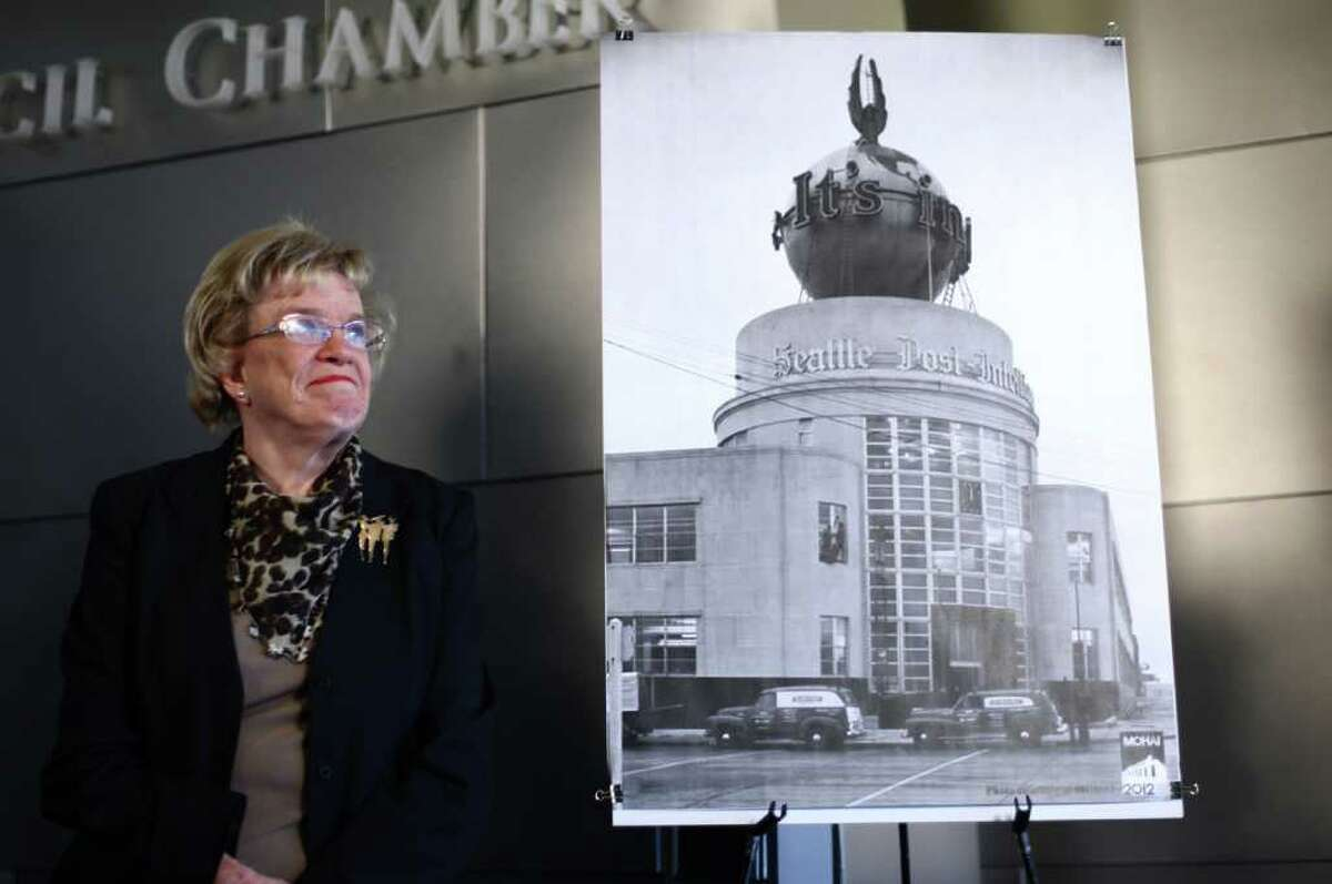 Seattle City Councilmember Jean Godden, a former newspaper columnist, stands next to a photograph of the Seattle P-I globe during a press conference announcing a plan to preserve the local landmark on Wednesday, March 7, 2012 at Seattle City Hall.