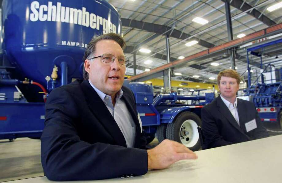 Robert Drummond, president of Schlumberger North America, (left) talks about his company as Jeremy Aumaugher, south division operations manager, listens to questions about expansion of their business to support clients in the Eagle Ford Shale. Photo: TOM REEL, San Antonio Express-News / San Antonio Express-News