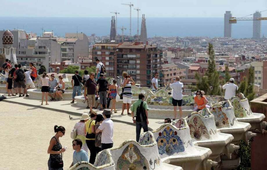 People walk on the terrace of Antoni Gaudi's Park Guell in Barcelona. Photo: Manu Fernandez / AP