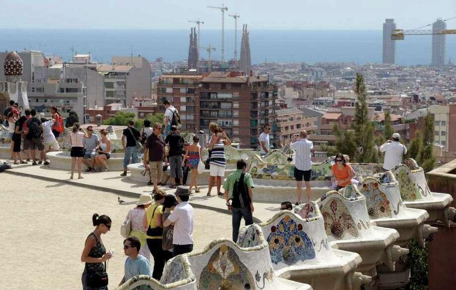 People walk on the terrace of Antoni Gaudi's Park Guell in Barcelona. Photo: Manu Fernandez / AP