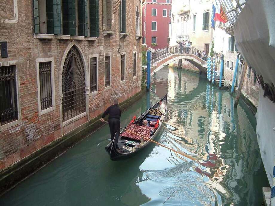 A solitary gondola maneuvers through the calm waters of a Venetian canal.   The price for a romantic gondola ride (for two people) is approximately 40 Euros. Photo: Brenda Renard / handout