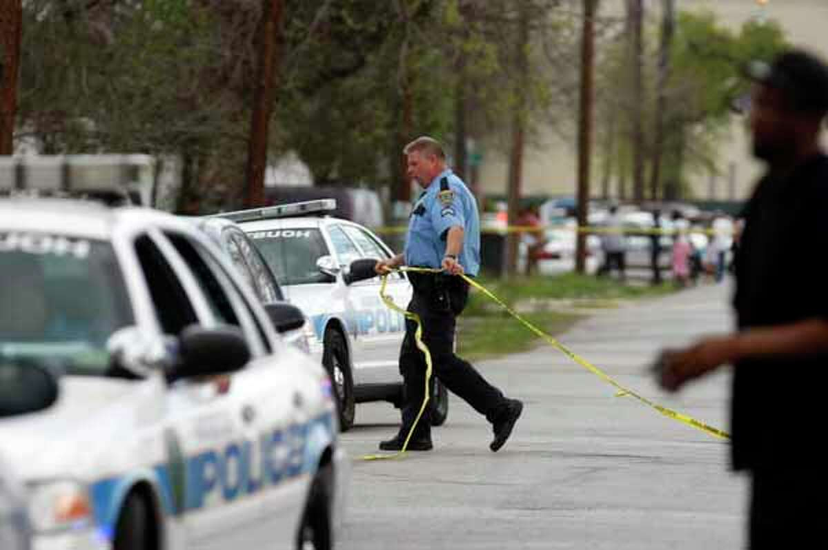 A police officer pulls crime scene tape at the scene where a man was fatally shot at a home in southeast Houston in 2012.