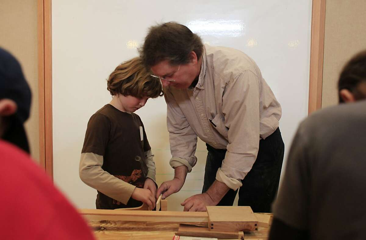 Composer and musical instrument creator Paul Dresher (right) helps Ronan Kelley (left), 9, build his instrument during the musical instrument building class at The Berkeley School on Wednesday, February 29, 2012 in Berkeley, Calif.