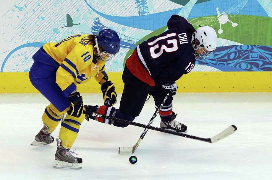 VANCOUVER, BC - FEBRUARY 22:  Julie Chu (#13) of the United States battles for the puck against Sweden's Emilia Andersson during the ice hockey women's semifinal game between USA and Sweden on day 11 of the Vancouver 2010 Winter Olympics at Canada Hockey Place on February 22, 2010 in Vancouver, Canada.  (Photo by Cameron Spencer/Getty Images) Photo: Cameron Spencer, ST / 2010 Getty Images