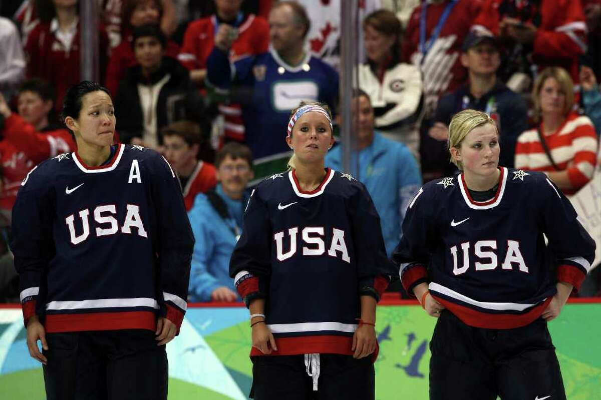 VANCOUVER, BC - FEBRUARY 25: (L to R) Dejected Team USA players Julie Chu #13, Kelli Stack #16 and Jocelyne Lemoreux #17 look on following their team's 2-0 defeat during the ice hockey women's gold medal game between Canada and USA on day 14 of the Vancouver 2010 Winter Olympics at Canada Hockey Place on February 25, 2010 in Vancouver, Canada. (Photo by Bruce Bennett/Getty Images)