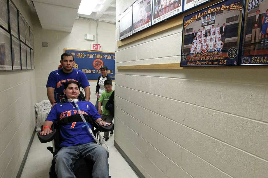 Eddie Moreno with assistance from his cousin Steven Cantu goes past a team photo of when Eddie played on the Alamo Heights High School basketball team on Wednesday, Mar. 7, 2012. Moreno had attended a school rally for the varsity basketball team that is headed to the state tournament for the first time in over two decades. Moreno who played on the team during the 2010-2011 season was paralyzed from a gunshot wound during a road-rage incident last March. The current varsity players met with Moreno before their practice after the rally. Kin Man Hui/Express-News. Photo: KIN MAN HUI, San Antonio Express-News / ©2012 San Antonio Express-News
