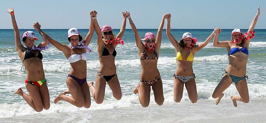 Spring breakers get airborne before a bikini parade in Panama City Beach, Fla. on Tuesday, March 6, 2012. Panama City Beach brought together women in an attempt to break the Guinness world record for the largest bikini parade on Tuesday. Photo: Andrew Wardlow, Associated Press