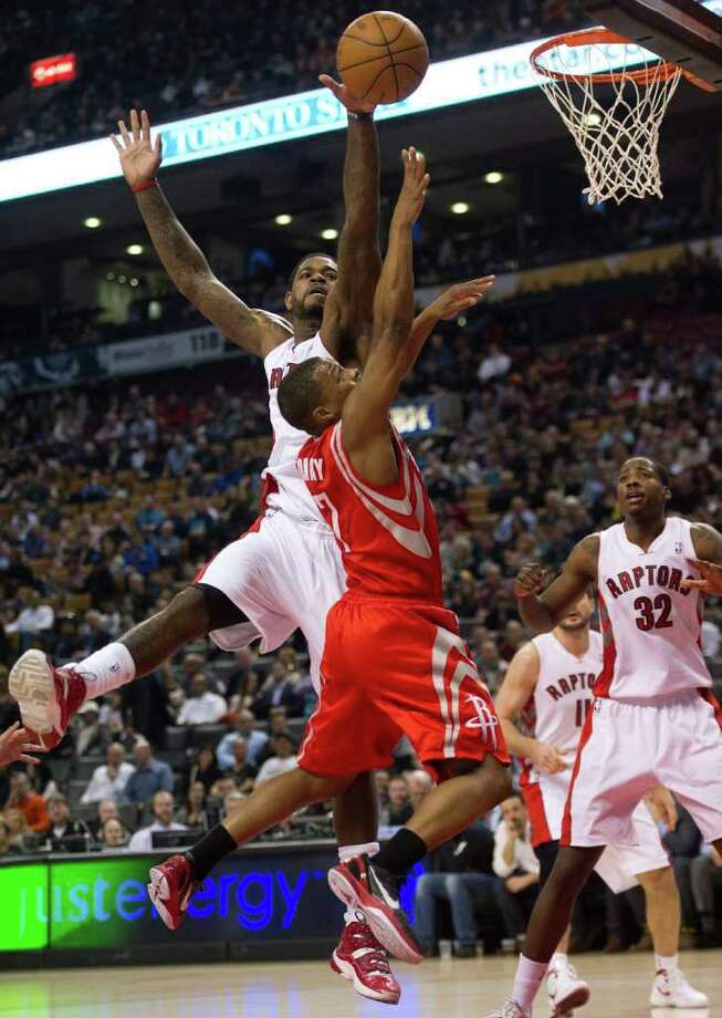 Toronto Raptors forward Amir Johnson, left, and Houston Rockets guard Kyle Lowry, center, reach for the ball during the first half of an NBA basketball game in Toronto on Wednesday, March 7, 2012. (AP Photo/The Canadian Press, Nathan Denette) Photo: Nathan Denette, Associated Press / The Canadian Press