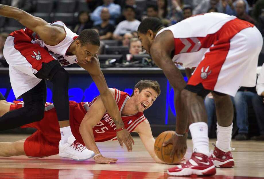 Toronto Raptors guard DeMar DeRozan, left, and forward Amir Johnson, right, reach for the loose ball against Houston Rockets forward Chandler Parsons during the first half of an NBA basketball game in Toronto on Wednesday, March 7, 2012. (AP Photo/The Canadian Press, Nathan Denette) Photo: Nathan Denette, Associated Press / The Canadian Press