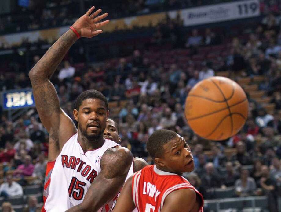 Toronto Raptors forward Amir Johnson, left, and Houston Rockets guard Kyle Lowry, right, watch a loose ball during the first half of an NBA basketball game in Toronto on Wednesday, March 7, 2012. (AP Photo/The Canadian Press, Nathan Denette) Photo: Nathan Denette, Associated Press / The Canadian Press