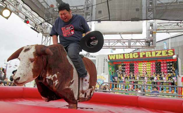 "Japanese Sumo wrestler Takuji Noro who competes as ""Noro"" rides a mechanical bull during a tour of The Houston Livestock Show & Rodeo Wednesday, March 7, 2012, in Houston. Photo: James Nielsen, Chronicle / © 2011 Houston Chronicle"