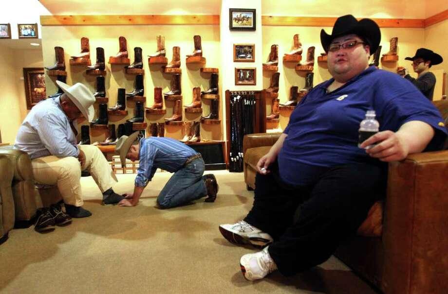 Sumo wrestler Byamba Ulambayar, left, has cowboy boots put on by Brian Pansky, next to Yamamotoyama Ryuichi at Pinto Ranch Fine Western Wear. Photo: Johnny Hanson, Houston Chronicle / © 2012  Houston Chronicle