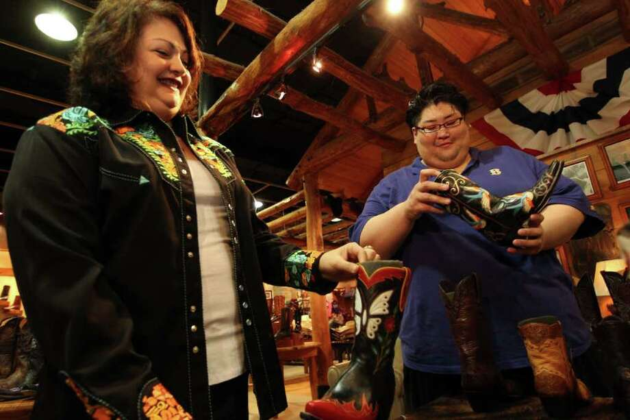 Sumo wrestler Yamamotoyama Ryuichi looks at a cowboy boot next to Bea Garcia, with Pinto Ranch as a group of sumo wrestlers were fitted with western wear. Photo: Johnny Hanson, Houston Chronicle / © 2012  Houston Chronicle
