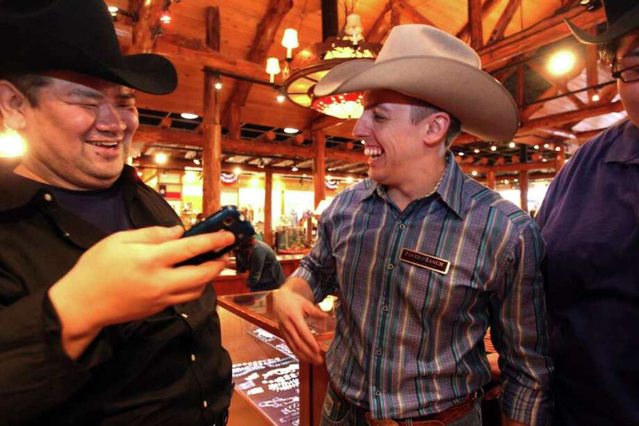Sumo wrestler Keisuke Kamikawa laughs with Pinto Ranch employee Brian Pansky as a group of sumo wrestlers were fitted with western wear at Pinto Ranch Fine Western Wear. Photo: Johnny Hanson, Houston Chronicle / © 2012  Houston Chronicle