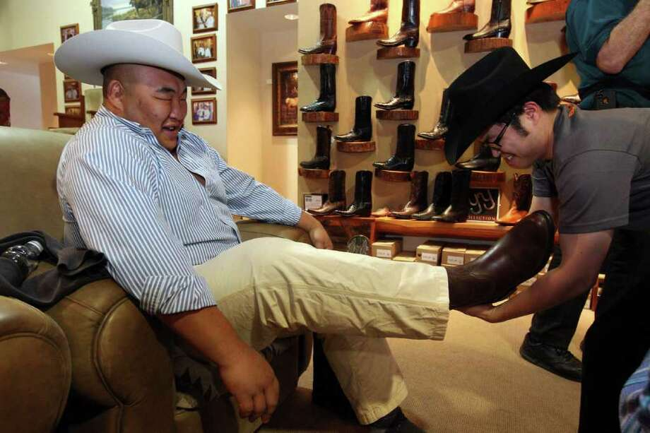 Sumo wrestler Byamba Ulambayar, has his cowboy boot pulled off by Sumo referee James Taku Leung at Pinto Ranch Fine Western Wear. Photo: Johnny Hanson, Houston Chronicle / © 2012  Houston Chronicle
