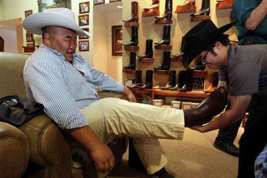 Sumo wrestler Byamba Ulambayar, has his cowboy boot pulled off by Sumo referee James Taku Leung at P