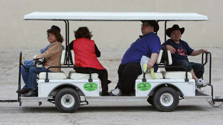 """Japanese Grand Sumo wrestlers Ryuichi Yamamoto 2nd from right, who competes as """"Yamamotoyama"""" and Takuji Noro right, who competes as """"Noro"""" ride a golf cart shuttle during a tour of The Houston Livestock Show & Rodeo Wednesday, March 7, 2012, in Houston. Photo: James Nielsen, Chronicle / © 2011 Houston Chronicle"""