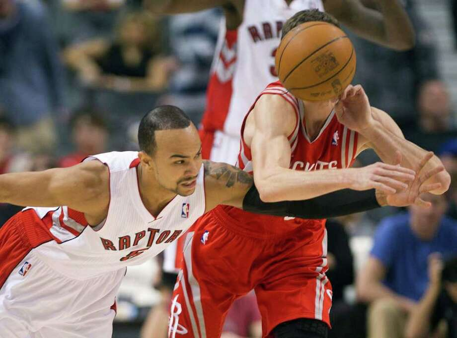 Toronto Raptors guard Jerryd Bayless, left, reaches for the ball next to Houston Rockets guard Goran Dragic during the first half of an NBA basketball game in Toronto on Wednesday, March 7, 2012. (AP Photo/The Canadian Press, Nathan Denette) Photo: Nathan Denette, Associated Press / The Canadian Press