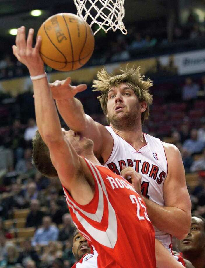 Toronto Raptors forward Aaron Gray, right, gets his arm onto the face of Houston Rockets forward Chandler Parsons during the first half of an NBA basketball game in Toronto on Wednesday, March 7, 2012. (AP Photo/The Canadian Press, Nathan Denette) Photo: Nathan Denette, Associated Press / The Canadian Press