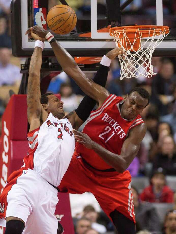 Toronto Raptors forward James Johnson, left, vies for the ball against Houston Rockets center Samuel Dalembert during the first half of an NBA basketball ganme in Toronto on Wednesday, March 7, 2012. (AP Photo/The Canadian Press, Nathan Denette) Photo: Nathan Denette, Associated Press / The Canadian Press
