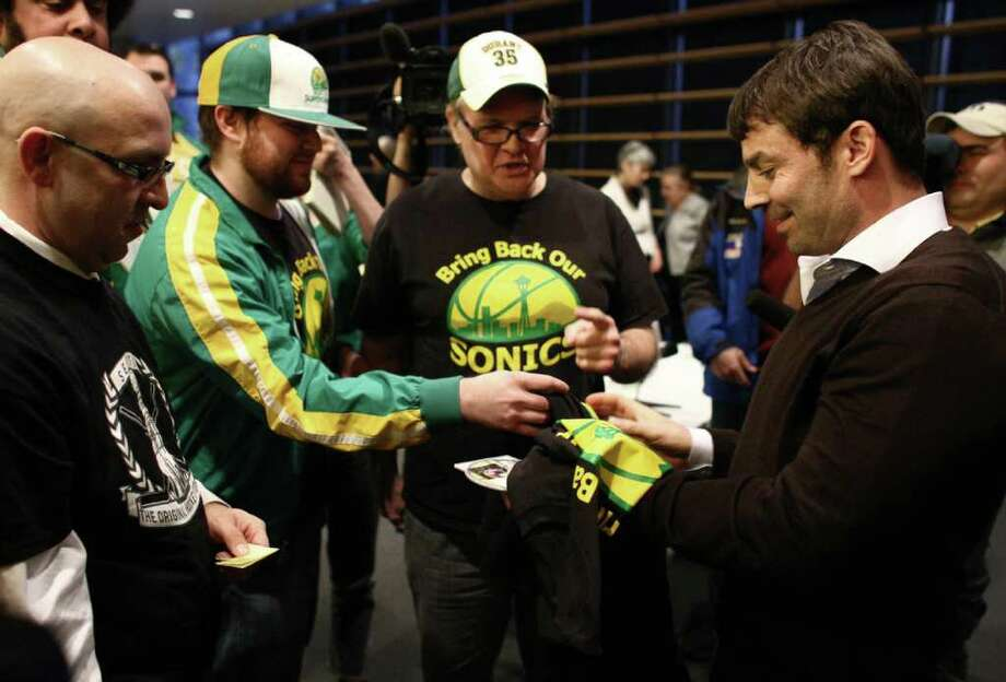 Bring Back Our Sonics co-founders David Brown, center, and Jeff Brown, left, present T-shirts to Seattle native Chris Hansen, who is leading a group of investors to bring NBA and NHL teams to Seattle. Hansen spoke before the city's Arena Review Panel on Wednesday, March 7, 2012, at Seattle City Hall. Photo: JOSHUA TRUJILLO / SEATTLEPI.COM