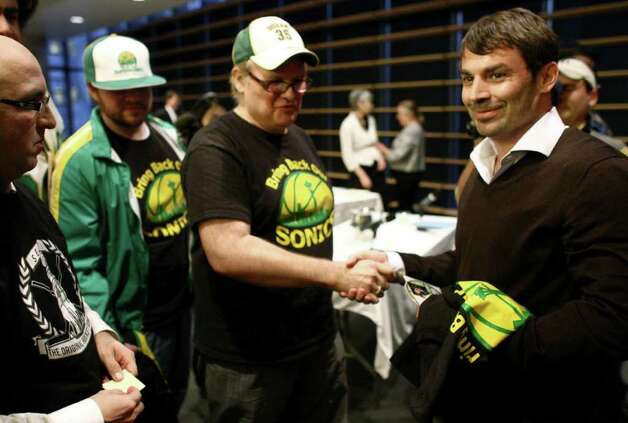 Bring Back Our Sonics co-founders David Brown, center, and Jeff Brown, left, present T-shirts to Seattle native Chris Hansen, who is leading a group of investors to bring a NBA and NHL team to Seattle. Hansen spoke before an Arena Review Panel on March 7, 2012, at Seattle City Hall. Photo: JOSHUA TRUJILLO / SEATTLEPI.COM