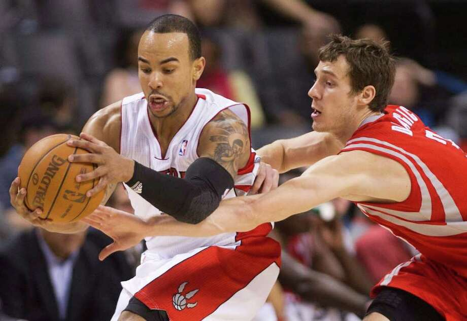 Toronto Raptors guard Jerryd Bayless, left, protects the ball from Houston Rockets guard Goran Dragic during the second half of an NBA basketball game Wednesday, March 7, 2012, in Toronto. (AP Photo/The Canadian Press, Nathan Denette) Photo: Nathan Denette, Associated Press / The Canadian Press