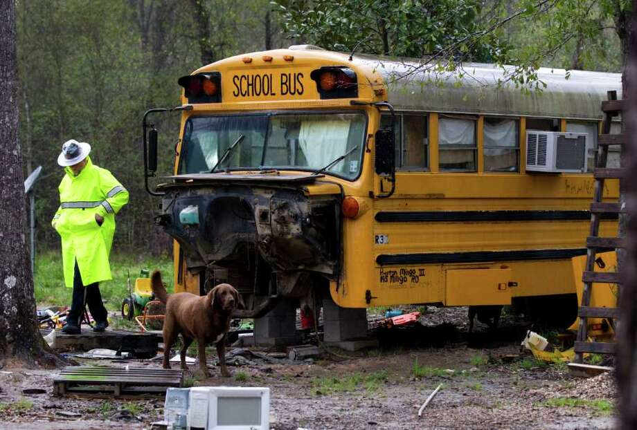 A Montgomery County sheriff's deputy steps through trash and junk surrounding an old school bus where two young children were found living unsupervised Wednesday in Splendora. The 11-year-old girl and her brother, 5, were taken into protective custody. Photo: Brett Coomer / © 2012 Houston Chronicle