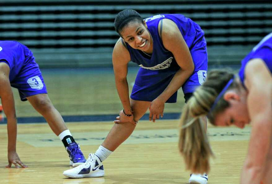 UAlbany women's basketball player Ebone Henry stretches with teammates during practice as the team p