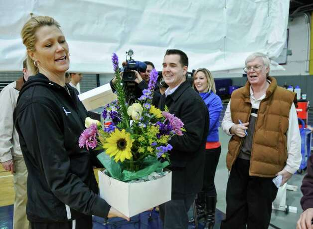 UAlbany women's basketball coach Katie Abrahamson-Henderson received flowers from former UAlbany women's coach Mari Warner, as she was talking to reporters after practice,  as her team prepares for Saturday's America East championship game, on Wednesday March 7, 2012 in Albany, N.Y.  (Philip Kamrass / Times Union ) Photo: Philip Kamrass / 00016703A