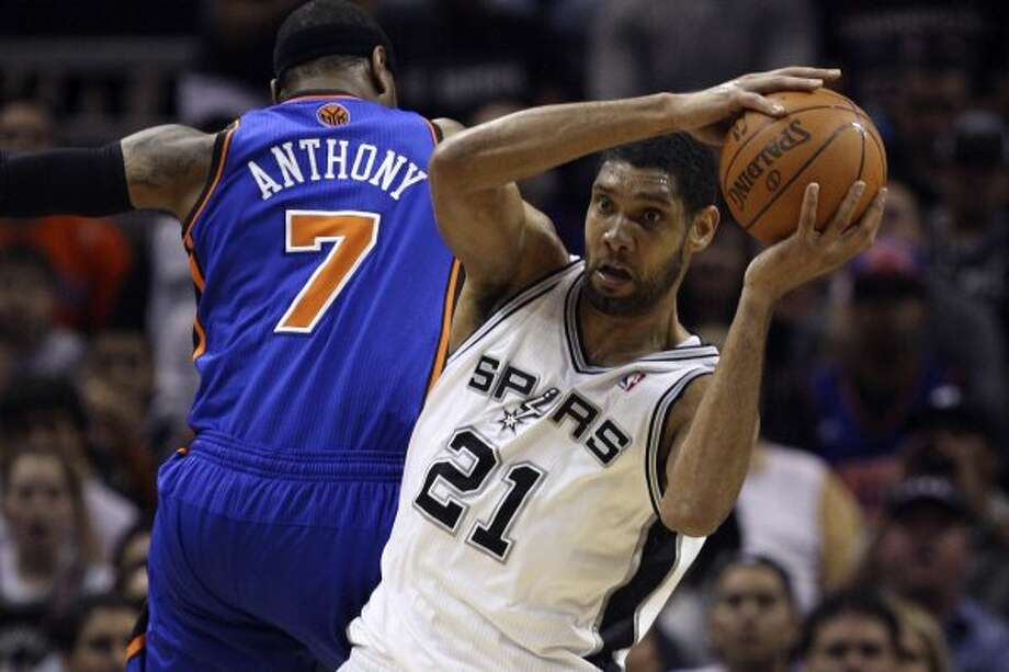 Spurs forward Tim Duncan rebounds the ball under pressure from the Knicks' Carmelo Anthony during the first half at the AT&T Center, Wednesday, March 7, 2012. Jerry Lara/San Antonio Express-News (Jerry Lara / San Antonio Express-News)