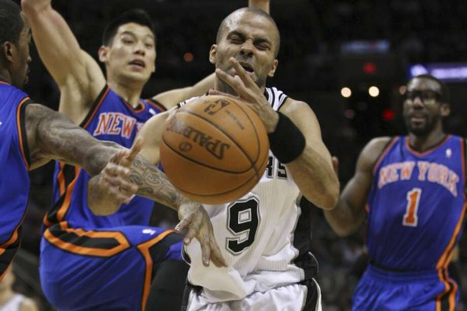 SPURS --  San Antonio Spurs Tony Parker is fouled by New York Knicks J.R. Smith, left, as Jeremy Lin, and Amar'e Stoudemire look on during the first half at the AT&T Center, Wednesday, March 7, 2012. Jerry Lara/San Antonio Express-News (Jerry Lara / San Antonio Express-News)