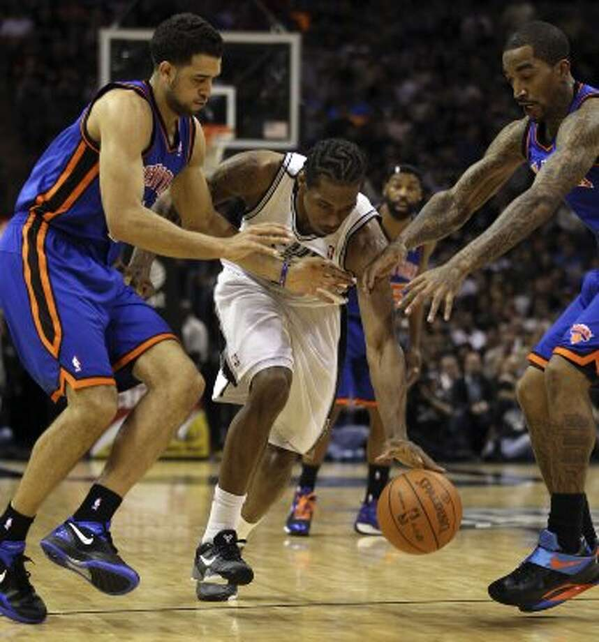 The Spurs' Kawhi Leonard cuts through the defense of the Knicks' Landry Fields (left) and J.R. Smith during the second half at the AT&T Center, Wednesday, March 7, 2012. The Spurs won 118-105. Jerry Lara/San Antonio Express-News (Jerry Lara / San Antonio Express-News)