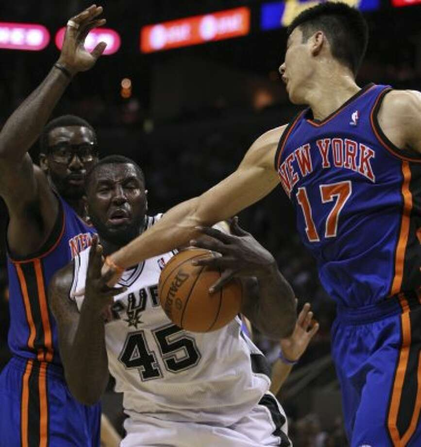 Spurs center DeJuan Blair grabs the rebound away from the Knicks' Amar'e Stoudemire (left) and Jeremy Lin during the second half at the AT&T Center, Wednesday, March 7, 2012. The Spurs won 118-105. Jerry Lara/San Antonio Express-News (Jerry Lara / San Antonio Express-News)
