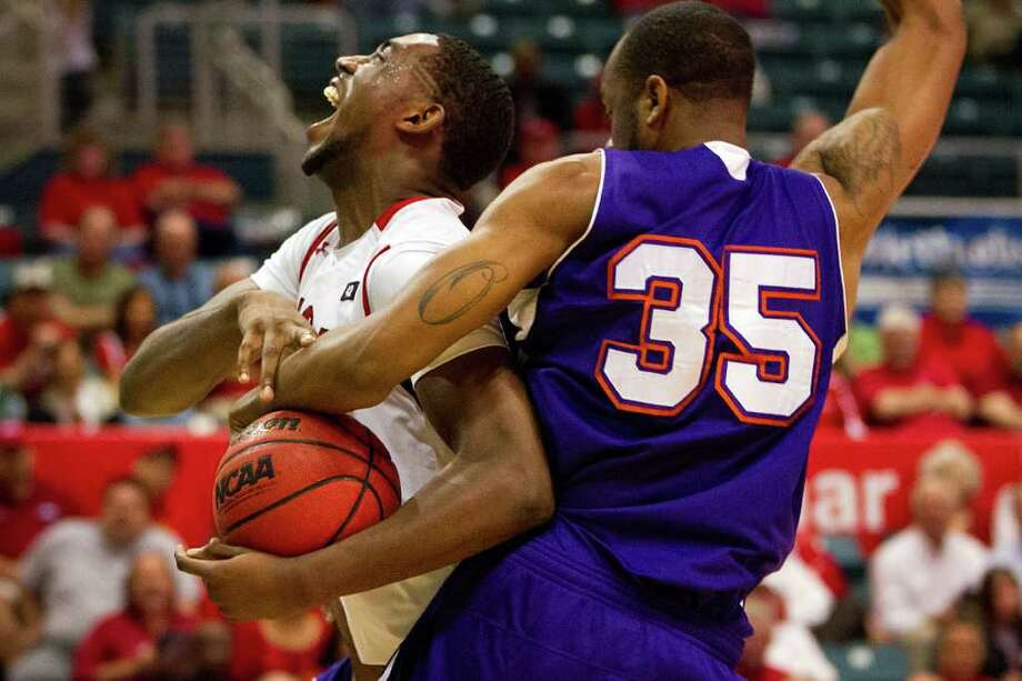 Lamar Cardinals forward Stan Brown (35) is wrapped up by Northwestern State Demons center O.J. Evans (35)  during the second half of a Southland Conference Tournament game at the Merrell Center on Wednesday, March 7, 2012, in Katy. Lamar won the game 76-69. ( Smiley N. Pool / Houston Chronicle ) Photo: Smiley N. Pool / © 2012  Houston Chronicle