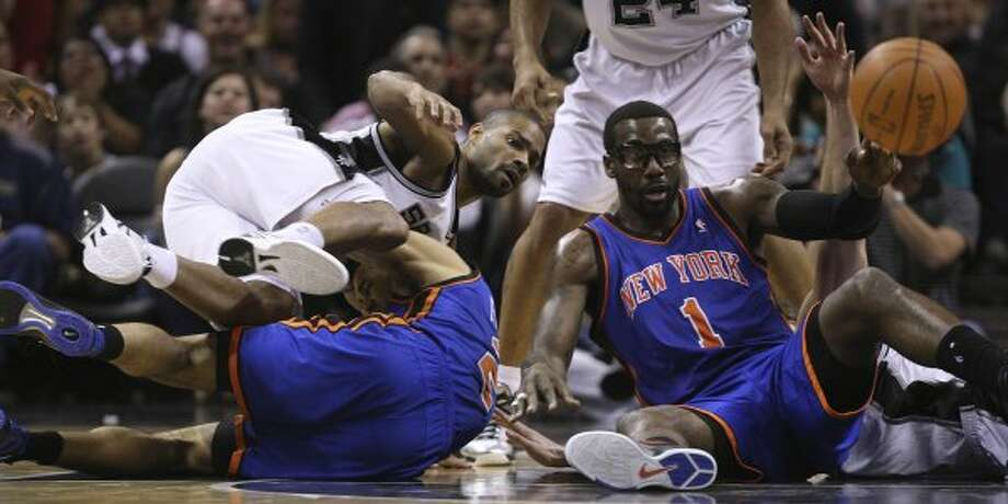 The Knicks' Amar'e Stoudemire (right) passes the ball as the Spurs' Gary Neal falls on Landry Fields during the first half at the AT&T Center, Wednesday, March 7, 2012. Jerry Lara/San Antonio Express-News (Jerry Lara / San Antonio Express-News)