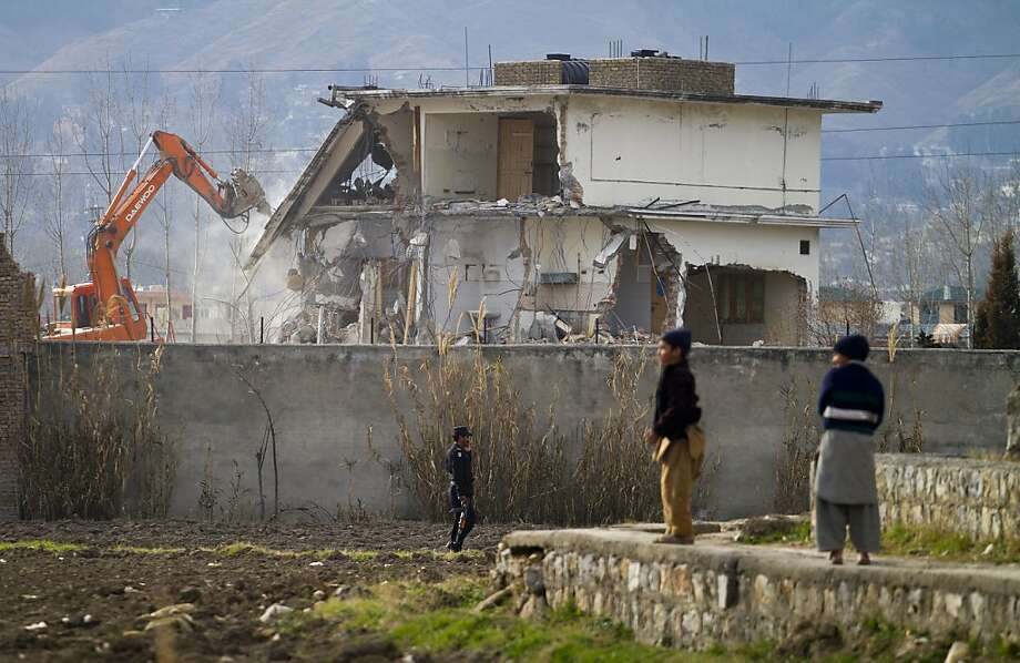 FILE- In this Feb. 26, 2012 file picture, a police commando stands guard as authorities use heavy machinery to demolish Osama bin Laden's compound in Abbottabad, Pakistan. Bin Laden spent his last weeks in a house divided, amid wives riven by suspicions. On the top floor, sharing his bedroom, was his youngest wife and favorite. The trouble came when his eldest wife showed up and moved into the bedroom on the floor below. (AP Photo/Anjum Naveed, File) Photo: Anjum Naveed, Associated Press