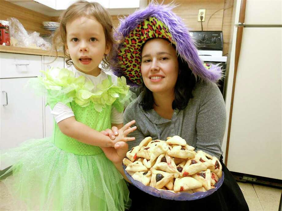 Rachel Rocklin, with daughter Ruth, hold a tray of fruit-filled pastries called hamantaschen, traditionally served during the observance of Purim during the Wednesday obervance at Congregation Ahavath Achim in Fairfield. Photo: Mike Lauterborn / Fairfield Citizen contributed